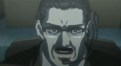 Souichirou Yagami, Light's father, talking into a headset while he stares intently at the screen