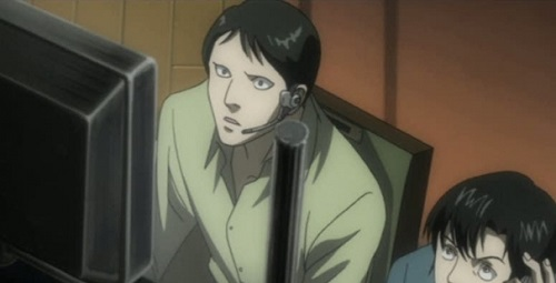 Hideki Ide staring at a computer screen while wearing a headset