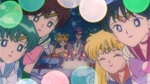 Minako Aino eyes shut and smiling, Rei Hino smiling and looking at Chibiusa, Mamoru Chiba standing behind birthday cake, Bishoujo Senshi Sailor Moon R